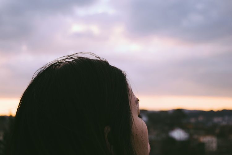 Cropped image of woman head against sky