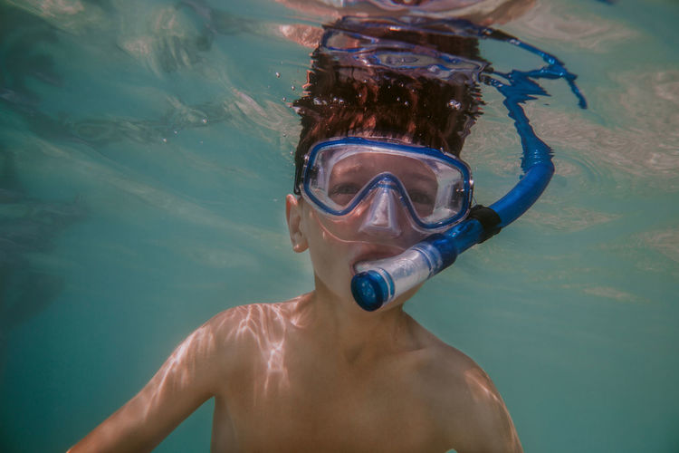 Child snorkeling. Young boy wearing diving mask and snorkel swimming under water. Snorkeling Snorkel Snorkelling Underwater Dive Sea Mast UnderSea Leisure Activity Sport Ocean Summer Holiday Vacation Outdoors Diver Swimming Goggles Gear Face Equipment Recreation  Exploring One Person Boy Child