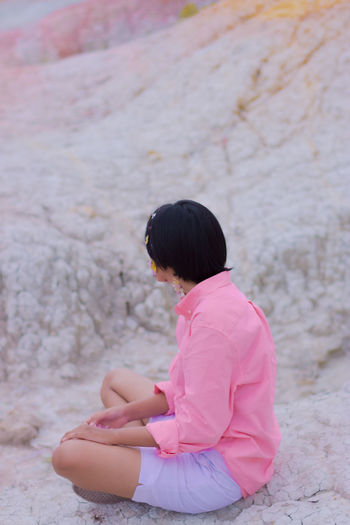 Rear view of woman sitting against pink wall