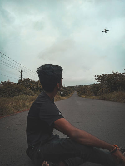 Side view of man looking at airplane against sky