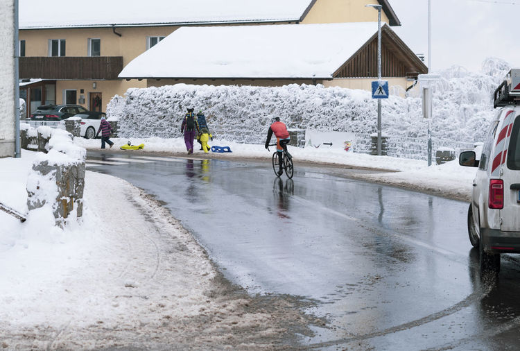 People on snow covered road during rainy season