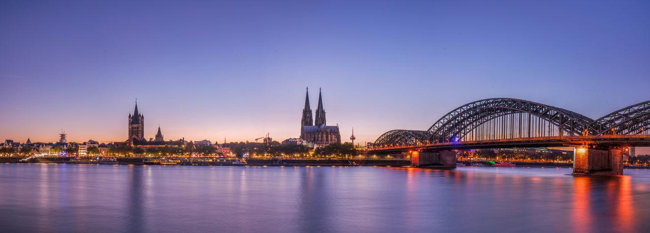 Illuminated bridge over river against sky in city at dusk