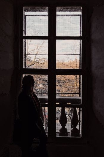 Silhouette Mid Adult Woman Looking Through Window While Standing At Home