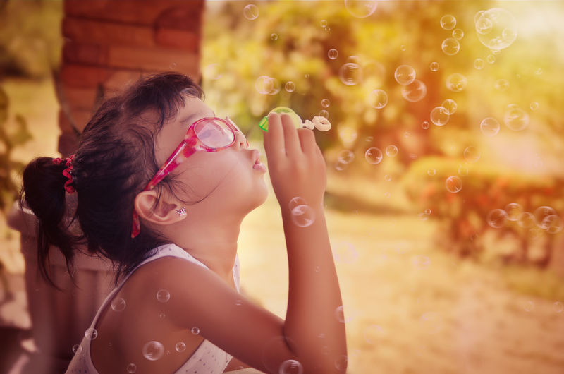Cute girl playing soap bubbles Blowing Bubbles Sunglasses Casual Clothing Child Girl Young Girl Bubbles Playing Happiness Enjoying The Sun Playing Alone Sunshine EyeEm Selects Human Hand Women Smiling Young Women Happiness Arts Culture And Entertainment Summer Close-up Hair Summer Road Tripping