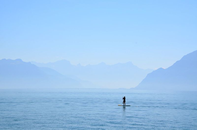 Silhouette person paddleboarding in sea against clear sky