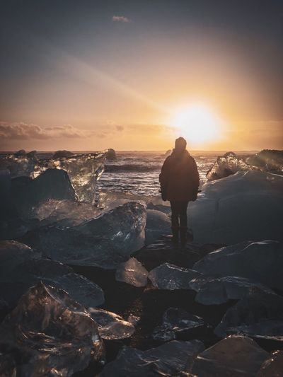 Person standing between icebergs at sea shore against sky during sunset