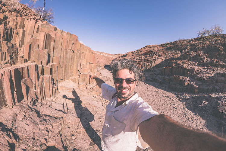 "Smiling man taking selfie at volcanic rock formation known as ""organ pipes"" in Damaraland, Namibia. Fisheye, toned image. Concept of adventure and exploration in Africa. Adult Arid Climate Beauty In Nature Clear Sky Day Human Hand Lifestyles Nature One Person Outdoors People Physical Geography Real People Rock - Object Rock Formation Smiling Sunglasses Young Adult Young Men"