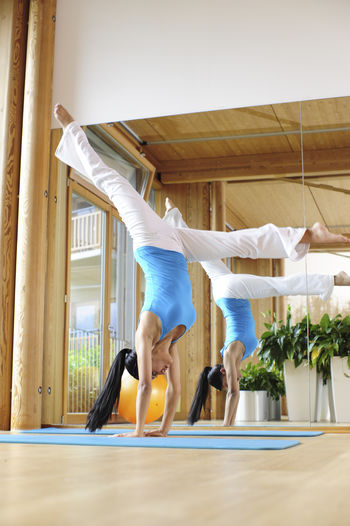 young beautiful sportive woman Balance Day Exercising Flexibility Full Length Gym Health Club Healthy Lifestyle Indoors  Lifestyles Men One Person People Real People Self Improvement Sports Clothing Upside Down Wellbeing Women Yoga Young Adult Young Women