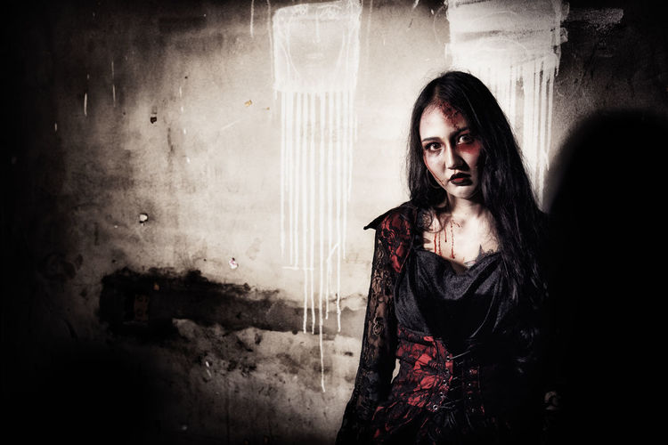 Portrait Of Young Woman With Spooky Make-Up Against Wall