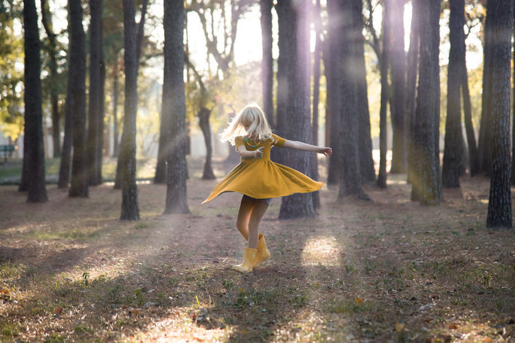 Girl Dancing Against Trees In Forest