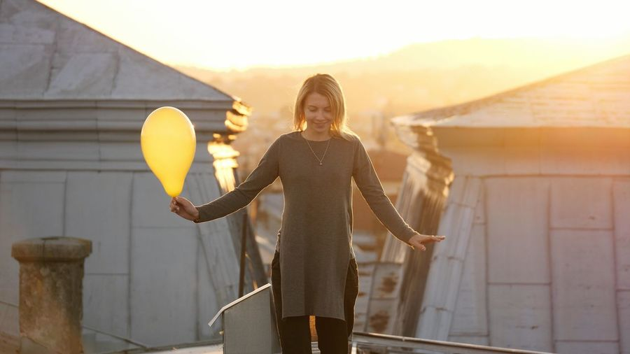 Portrait of attractive young woman feeling happy while listening music in the headphone, singing and dancing on a rooftop during sunset. Freedom Happy Woman Young Architecture Front View Leisure Activity Lifestyles One Person Outdoors Real People Relax Young Adult Young Women