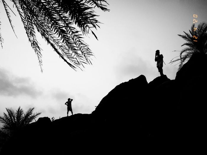 Low angle view of silhouette people standing on rock against sky