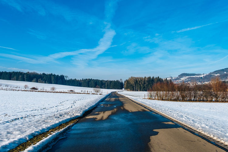 Empty Road Amidst Snow Covered Field Against Sky