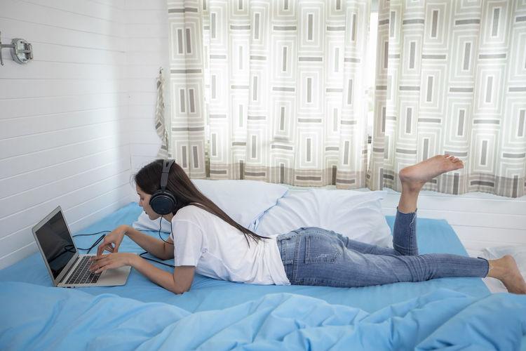 Full length of senior woman lying down on bed