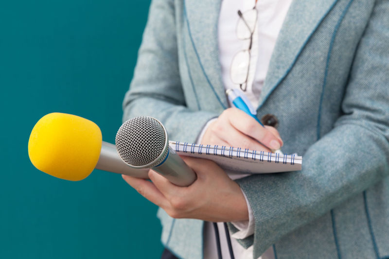 Midsection of female reporter holding microphone