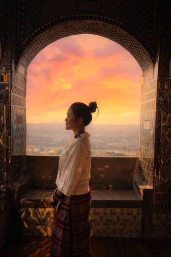 Side view of woman standing against window and sky during sunset