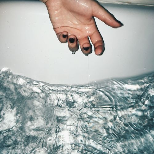 Midsection of person splashing water in bathroom