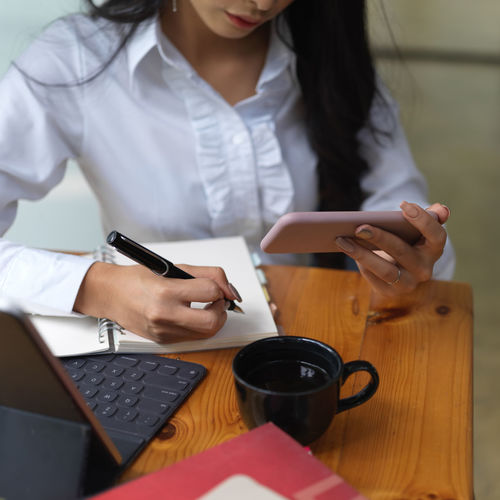Midsection of woman using phone while writing on book at office