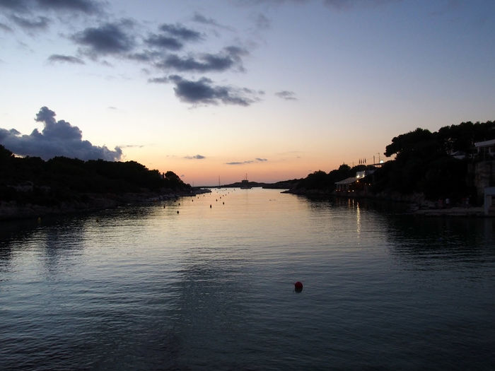 The cala santandria in ciutadella at twilight with a glowing evening sky reflected in dark calm Water Sky Sunset Scenics - Nature Beauty In Nature Tranquility Tranquil Scene Waterfront Tree Nature Reflection Cloud - Sky No People Sea Outdoors Dusk Plant Silhouette Bay Of Water Resort Concept Menorca