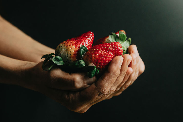 Cropped image of hand holding strawberry against black background