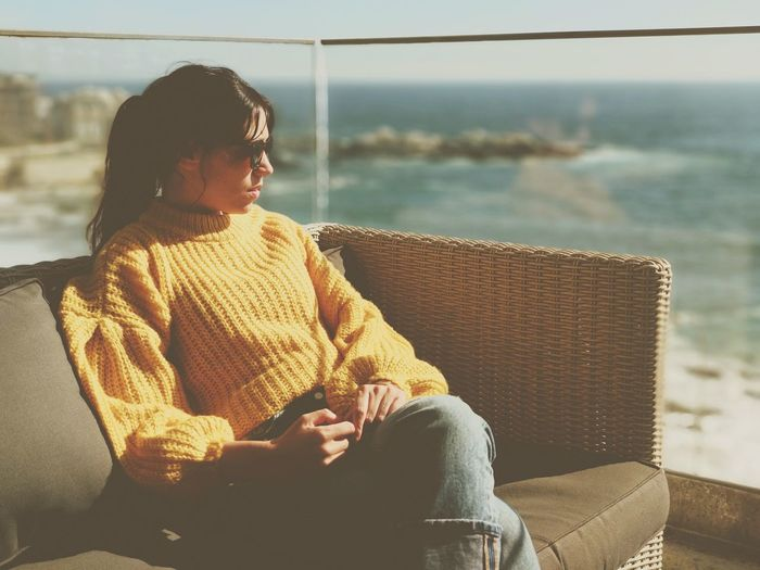 Woman sitting on sofa in balcony against sea