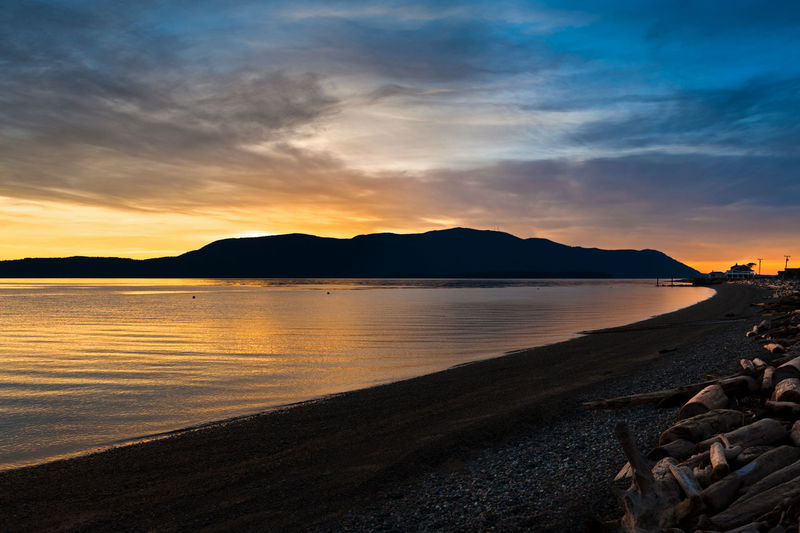 Scenic View Of Beach At Orcas Island Against Cloudy Sky During Sunset