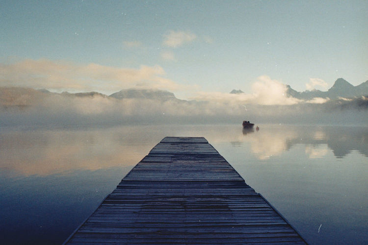 Jetty over lake against sky