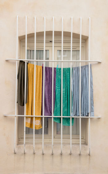 Close-up of multi colored clothes over behind bars