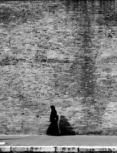 Woman walking on sidewalk against brick wall