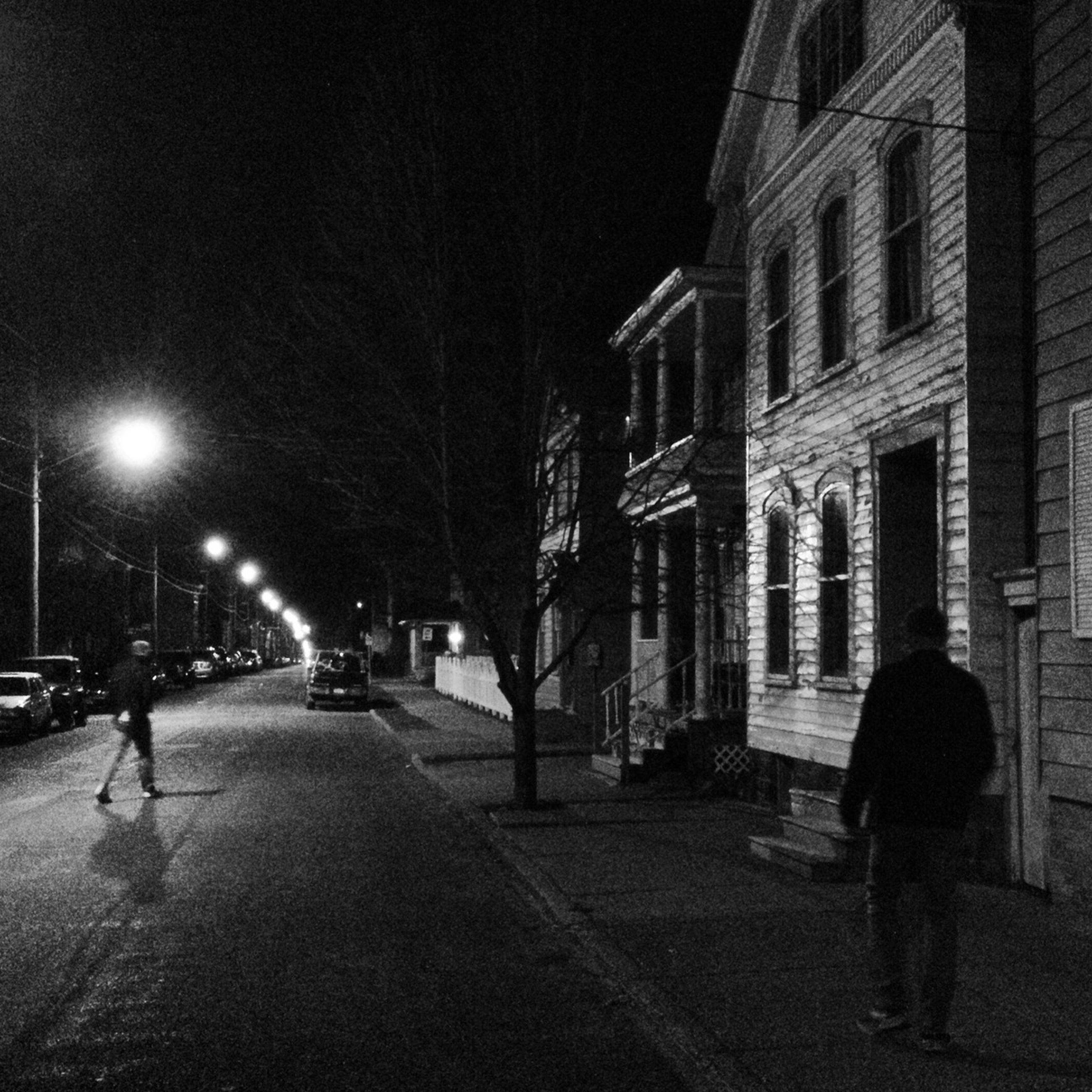 building exterior, architecture, built structure, street, night, walking, illuminated, street light, the way forward, city, men, building, full length, lifestyles, city life, unrecognizable person, road, incidental people