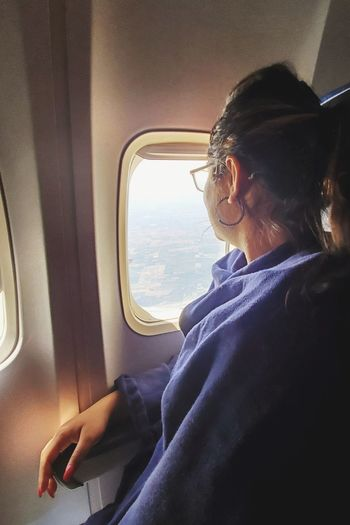 Midsection of woman sitting in airplane