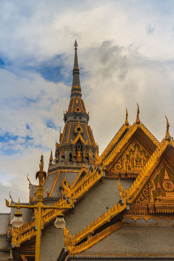 Beautiful Thai's style craving and decoration on the golden gable end at Wat Sothonwararam, a famous public temple in Chachoengsao Province, Thailand. Buddhism Temple Chachoengsao Chachoengsao Province Cloudy Day Cloudy Sky Dramatic Sky Gable End Golden Temple Thai's Style WAT Sothon Wara RAM Worawihan (WAT Luang PHO Sothon) Wat Sothon Wat Sothon Wararam Worawihan Architecture Belief Buddhist Temple Building Building Exterior Built Structure Cloud - Sky Cloudy Sunset Cloudysky Dramatic Landscape Dramatic Skies Gable Gable Roof Gable Temple Naga Gables Golden Gable History Low Angle View Nature No People Ornate Outdoors Place Of Worship Religion Sky Spire  Spirituality The Past Tower Travel Travel Destinations Wat Sothonwararam White Clouds And Blue Sky