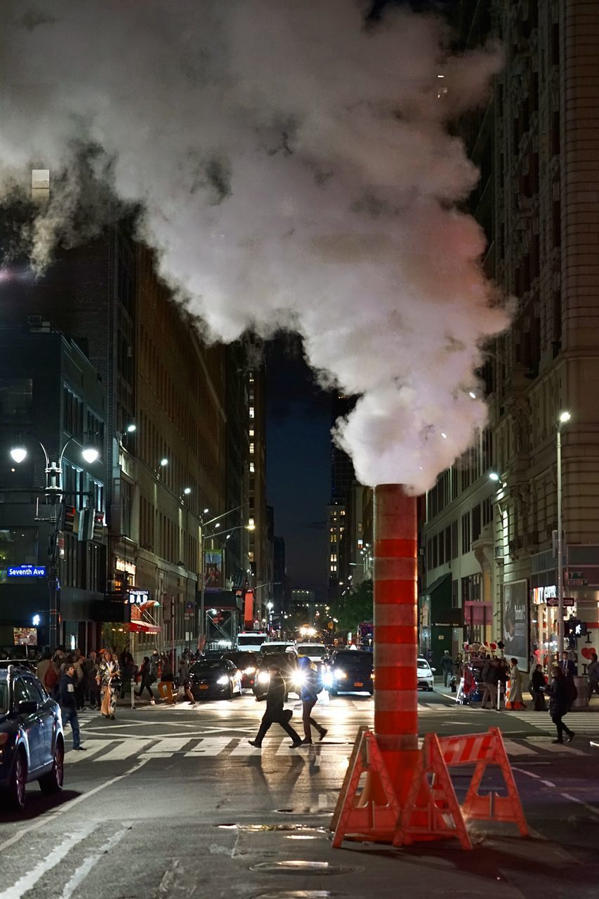 city, architecture, building exterior, street, built structure, transportation, night, road, smoke - physical structure, city life, pollution, illuminated, sky, city street, air pollution, group of people, incidental people, motion, industry, outdoors, office building exterior
