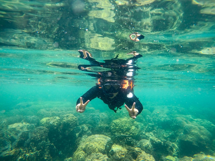 Person Showing Peace Sign While Scuba Diving In Sea