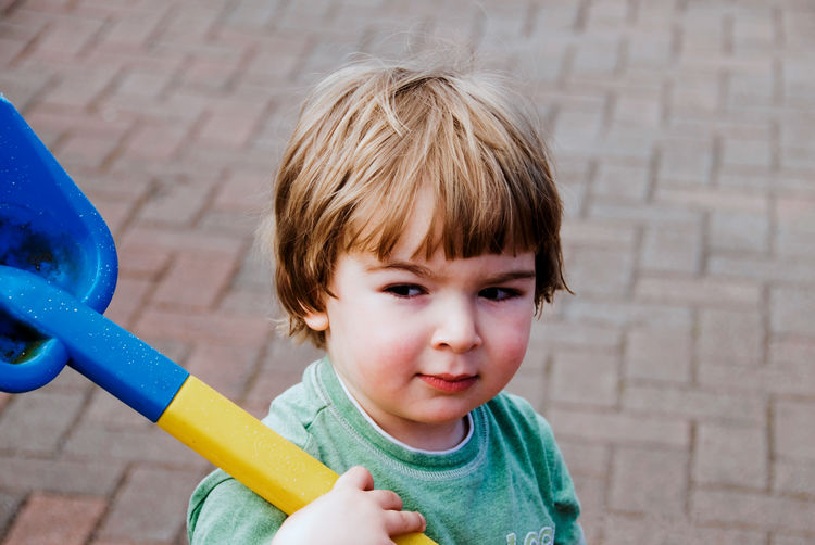 High angle view of boy looking away while holding toy on footpath