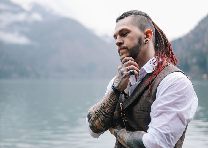 A brutal male hipster groom in a wedding suit in nature by the mountains and lake