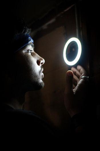 Portrait of man holding camera in darkroom