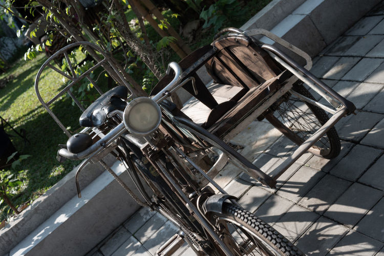 High angle view of old bicycle parked by tree