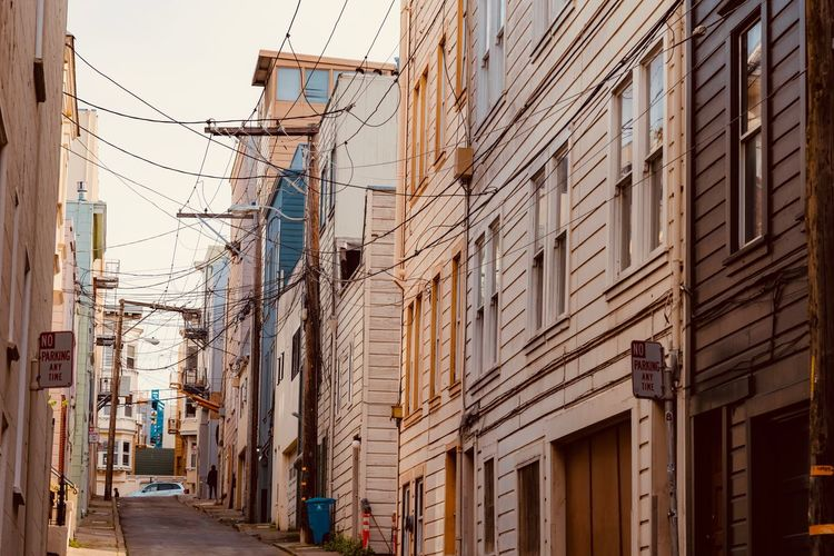Architecture Building Exterior Built Structure City Building Street Residential District Transportation Day Incidental People Nature Outdoors Low Angle View Direction Cable Road Sky Mode Of Transportation The Way Forward Complexity Power Supply Apartment