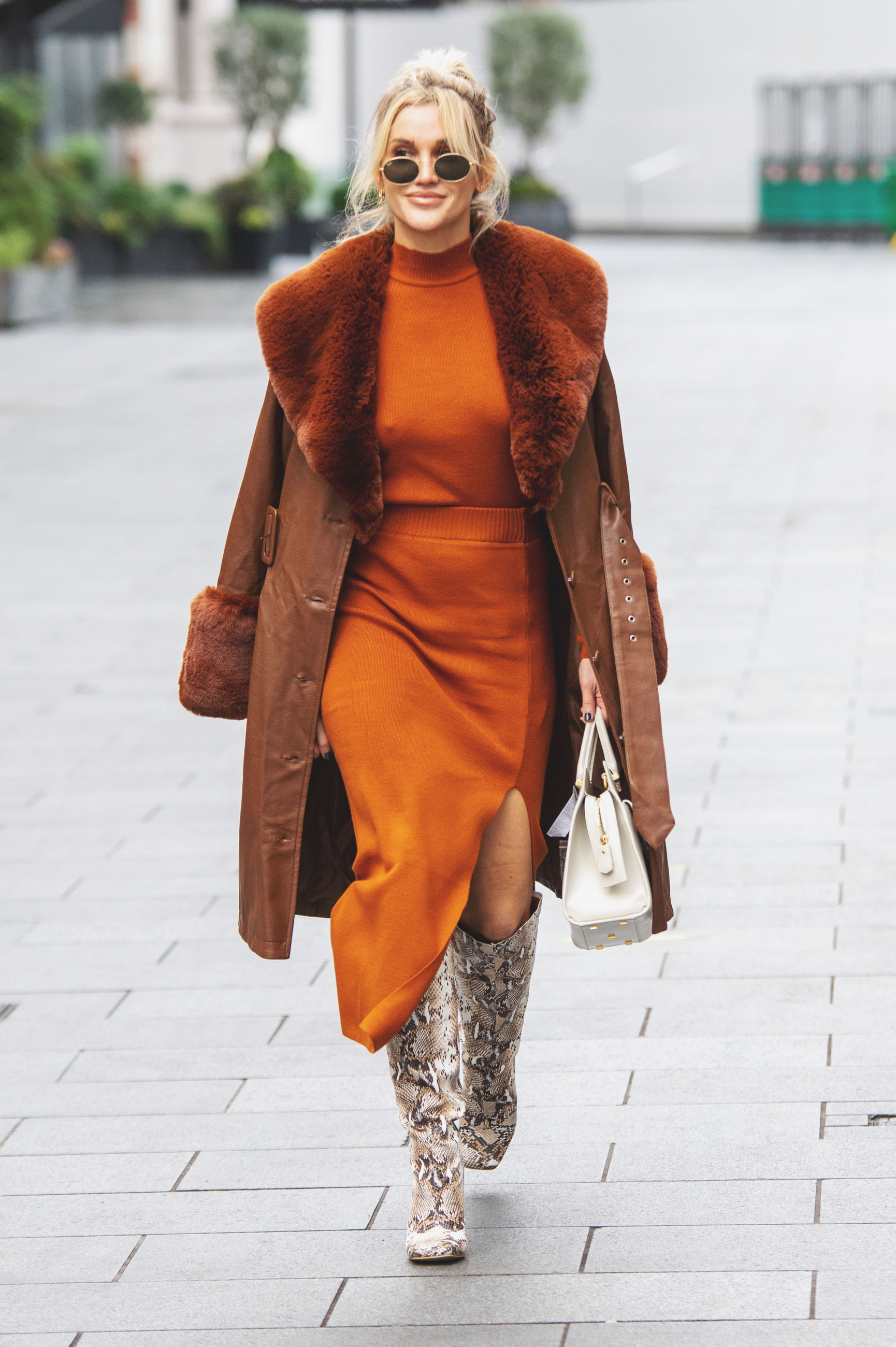 adult, fashion, clothing, one person, women, city, architecture, walking, coat, portrait, street, full length, city life, footpath, young adult, smiling, lifestyles, bag, spring, happiness, footwear, outerwear, female, front view, elegance, outdoors, trench coat, day, dress, looking at camera, standing, yellow, arts culture and entertainment, nature, sidewalk, casual clothing, hairstyle, emotion