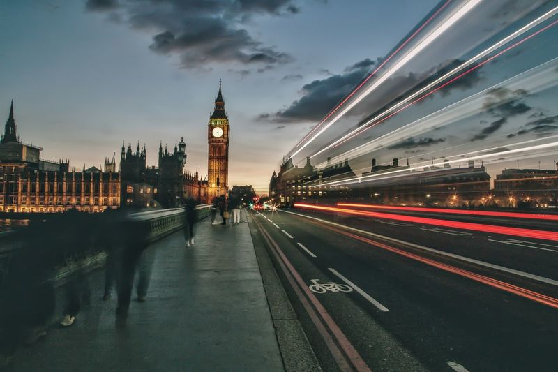 Light trails on road against big ben during sunset in city