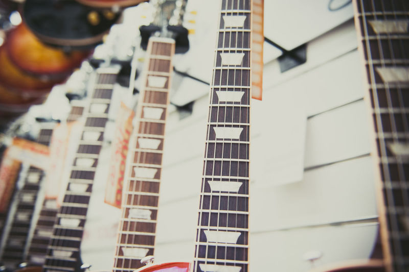 Guitar exposed in store showroom Chords Fretboard Guitar Neck In A Row Many Music Musical Instrument Selective Focus Shop Showroom Sound Store String Stringed Instrument Wooden