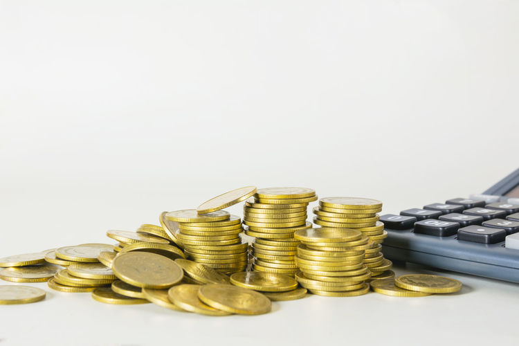 Stack of coins by calculator against white background