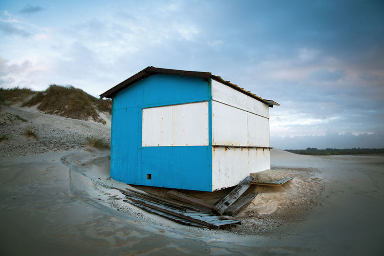 Undermined Architecture Beach Blue Building Built On Sand Built Structure Closed Cloud - Sky Danger Danger Of Collapsing Day Hut Land Landscape Nature No People Outdoors Sand Sand Dune Sky Unstable Water Wood - Material Wooden House