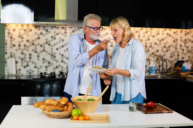 Man feeding food to his wife in kitchen