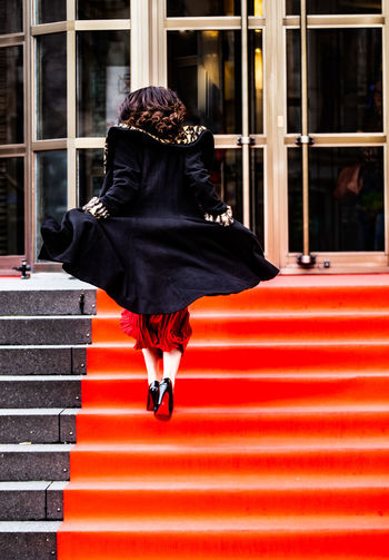Rear view full length of woman moving up on steps