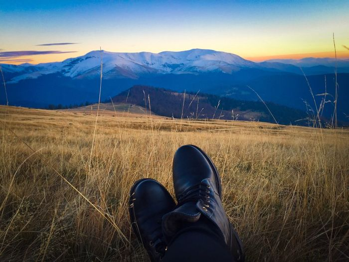 Black boots and snowcapped mountains in the background at sunset
