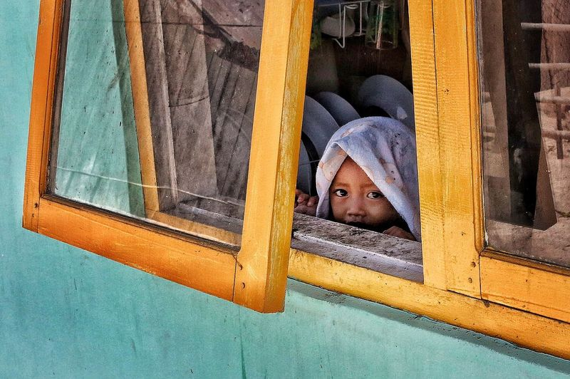 Portrait of an Indonesian kid observing from the window in Flores Island. Photo: @ignasirodriguez Child Colors Flores Flores Island Green Hidden Indoneisa Kid Kids Portrait Travel Travel Photography Window Yellow