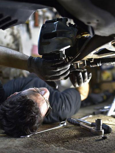 Close-up of man repairing car in workshop