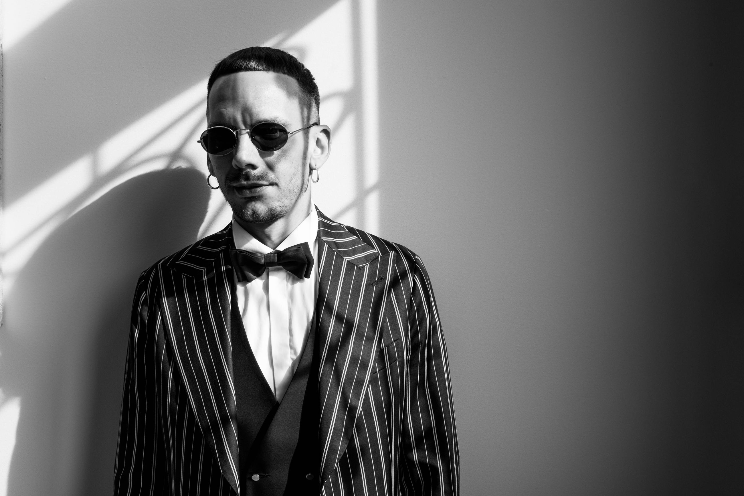 one person, front view, glasses, indoors, bow tie, standing, portrait, waist up, fashion, young men, young adult, looking at camera, real people, sunglasses, lifestyles, men, formalwear, business, confidence, menswear